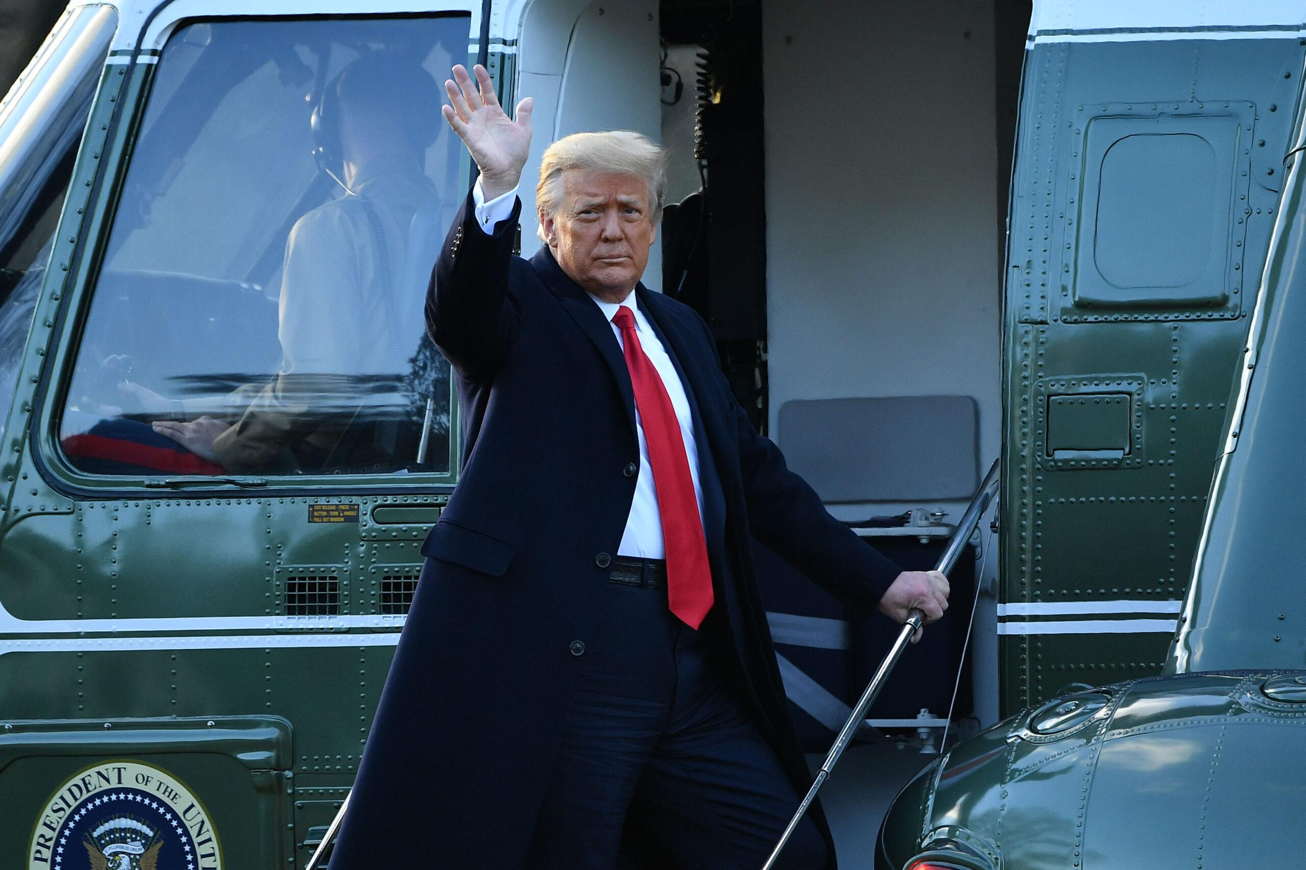 Donald Trump saluda desde la escalera del helicóptero al dejar su cargo de presidente de EU