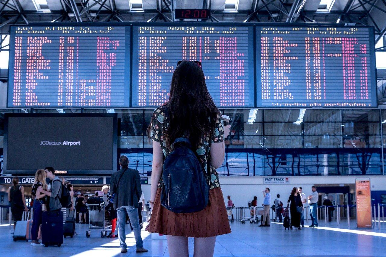 una joven mirando las pantallas de en aeropuerto